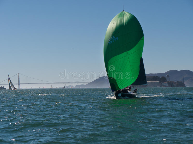 Sailboat with spinnakers at Rolex Cup. Sailboat with spinnakers competing at Rolex Cup sailing event in San Francisco September 2015. Golden Gate bridge in the stock images