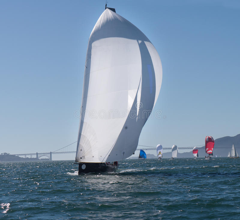 Sailboat with spinnakers at Rolex Cup. Sailboat flying spinnaker competing at Rolex Cup sailing event in San Francisco September 2015. Golden Gate bridge in the royalty free stock photo