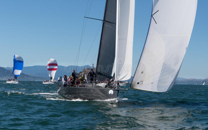 Sailboat with spinnakers at Rolex Cup. Sailboat flying spinnaker competing at Rolex Cup sailing event in San Francisco September 2015. Golden Gate bridge in the royalty free stock photos