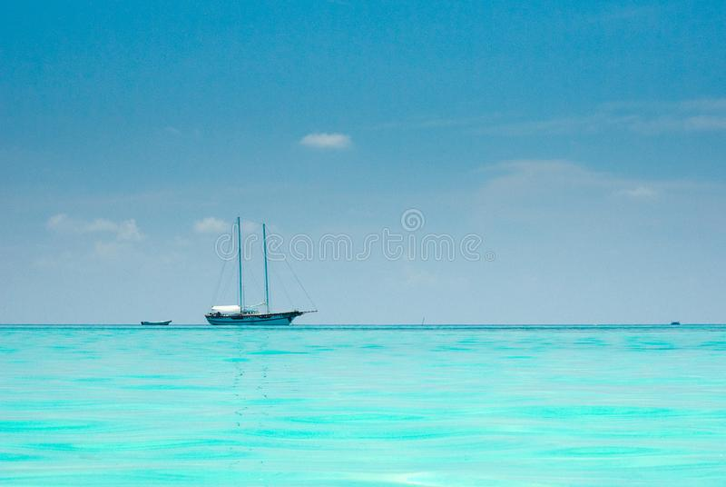 A sailboat on still water. A sailboat standing still on horizon line royalty free stock photo