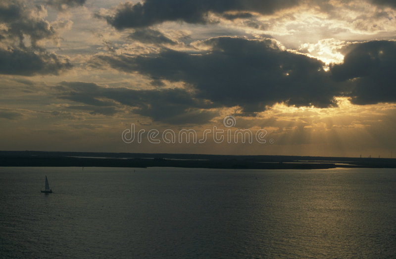 Sailboat at sunset. Sailboat coining into Brunswick harbor at sunset royalty free stock photo
