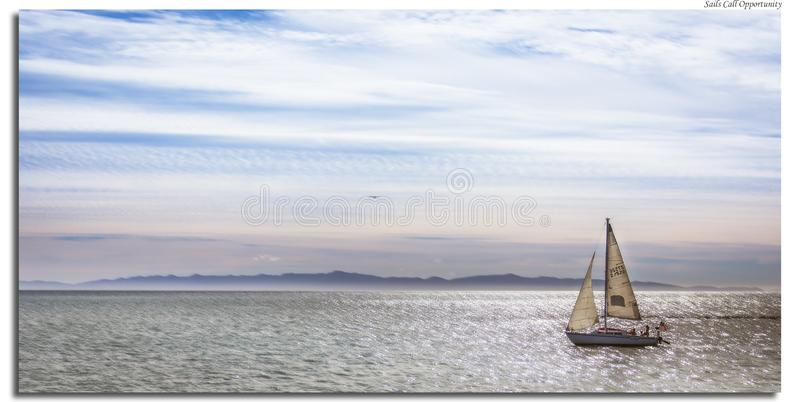 Sailboat in the water. During the sunrise hour and a nice cloudy and sunny day.  landscape shows the boat sailing away royalty free stock images
