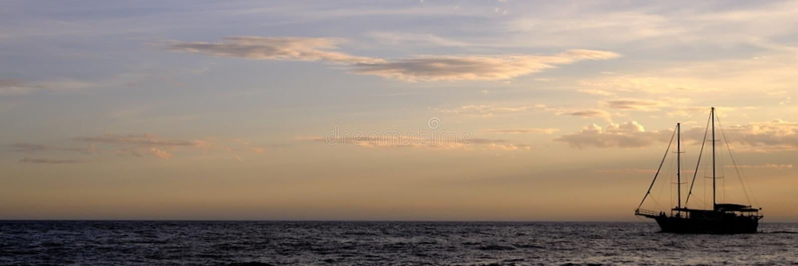 Sailboat on water at sunset royalty free stock photo