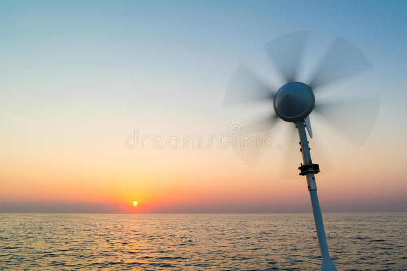 Sailboat with wind turbine sailing on North Sea at sunset, Nethe royalty free stock photography