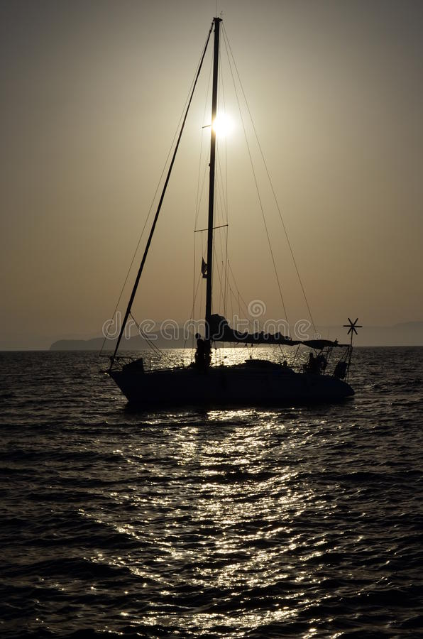Sailboat with windmill crossing the sun. Photo is take from Chania port at Crete, Greece. Sun is about to set. Pole is crossing the sun stock images