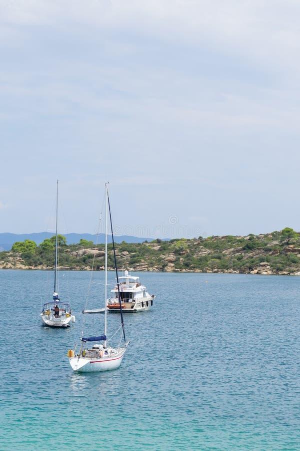 Sailboats που δένονται κοντά στην ακτή μπροστά από τους βράχους και τη βλάστηση στοκ φωτογραφία με δικαίωμα ελεύθερης χρήσης