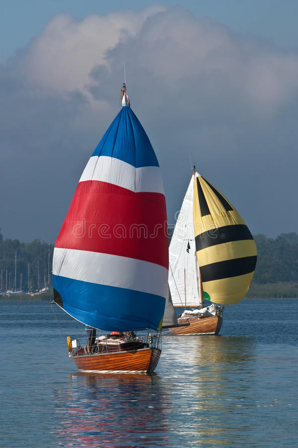 Sailboats. With colored spinnakers goes away stock image