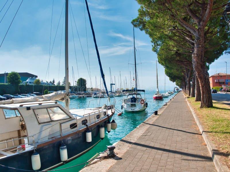 Sailboats anchored along the lungolago Giuseppe Garibaldi in the village of Peschiera del Garda on Lake Garda, Italy stock photos