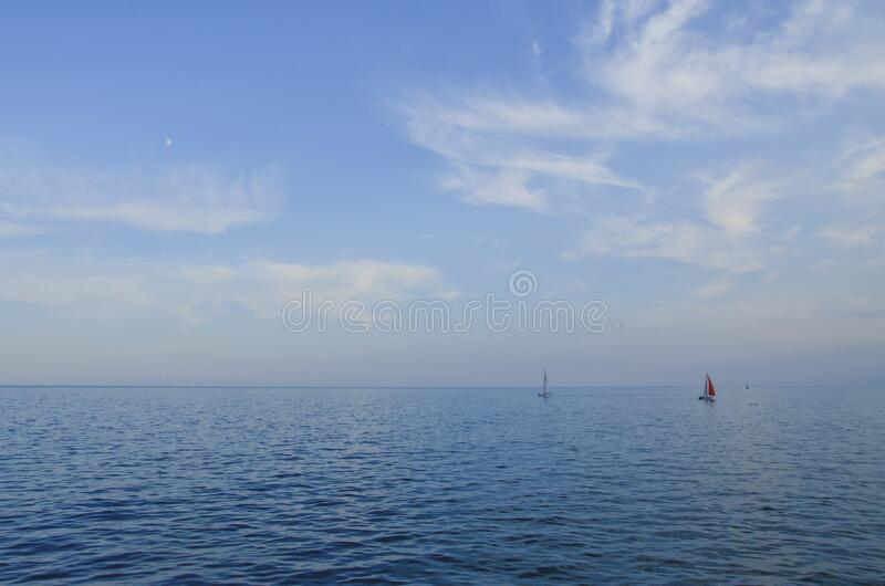 Sailboats on calm blue sea royalty free stock photo