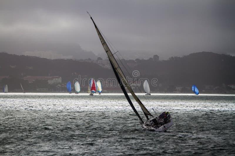 Bay Sailing; Breezy Conditions on San Francisco Bay. Sailboats cross San Francisco Bay with patchy clouded sky. San Francisco, California, USA royalty free stock photo