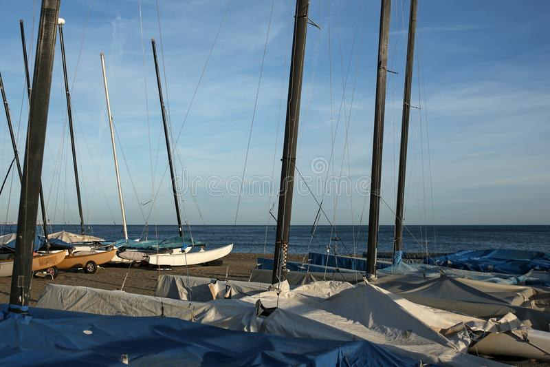 Sailboats on empty beach. At dusk stock image