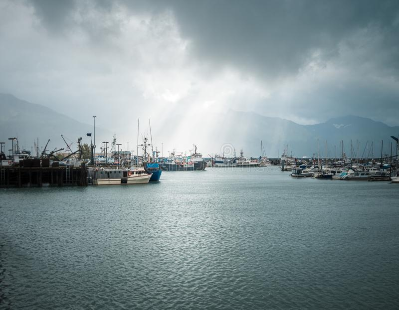 Sailboats in the harbor with sun rays coming down from a stormy Seward sky stock photo