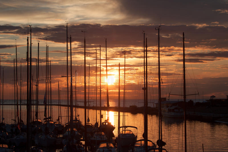 Sailboats in harbor with sunset. And clouds royalty free stock photo