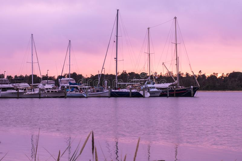 Sailboats in a Harbor at Sunset. Several sailboats in a harbor at sunset.  Sunset has a beautiful purple and pink tone stock image