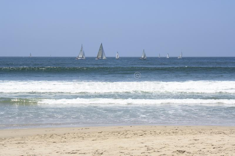 Sailboats on the horizon of a blue ocean stock photography