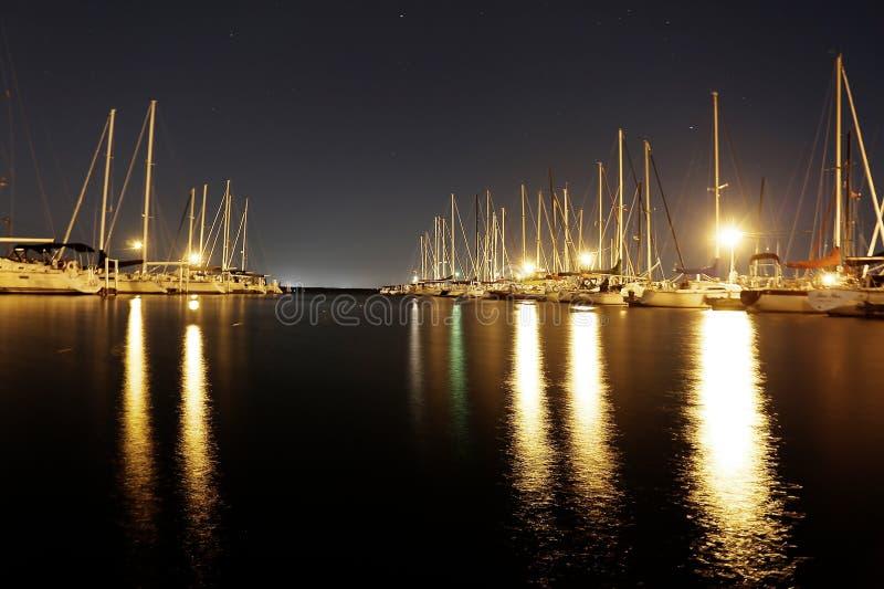 Sailboats illuminated in harbor royalty free stock photo
