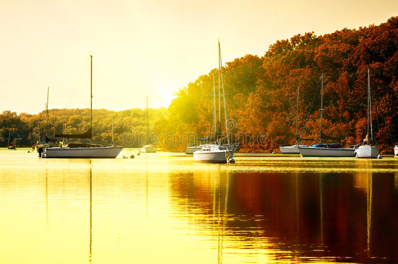 Sailboats on lake at sunset stock photo