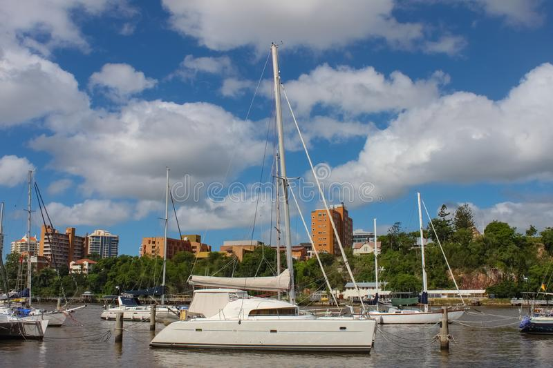 Sailboats moored in the Brisbane River under a beautiful blue sky with white clouds and building on the South Bank of Brisbane stock photo
