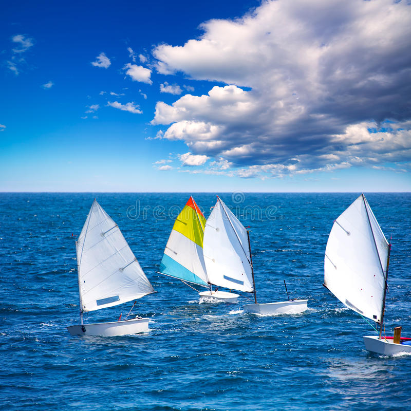 Sailboats Optimist learning to sail in Mediterranean at Denia. Little sailboats Optimist learning to sail in Mediterranean at Denia Alicante royalty free stock photos