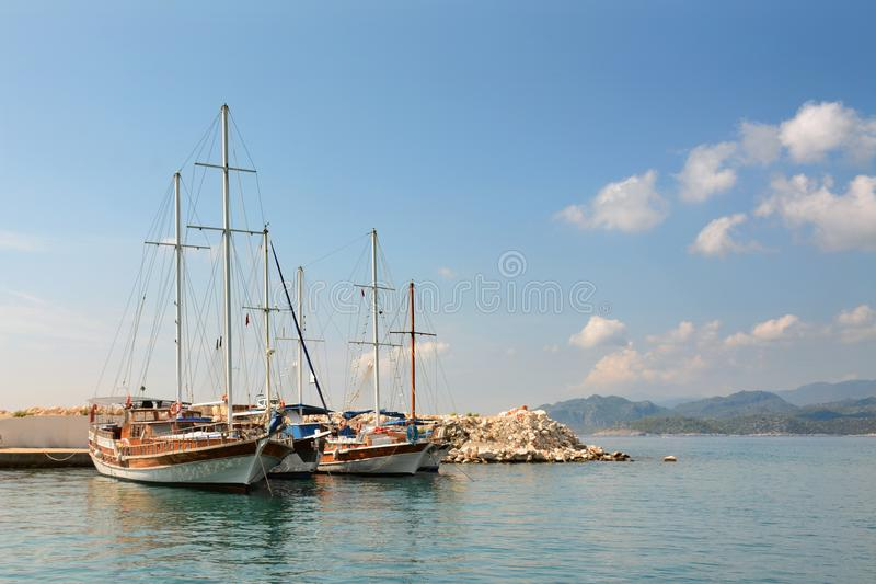 Sailboats on pier. Calm sea water and blue sky background. Copy space stock image