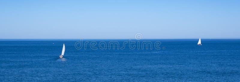 Sailboats sailing in the blue sea royalty free stock photos