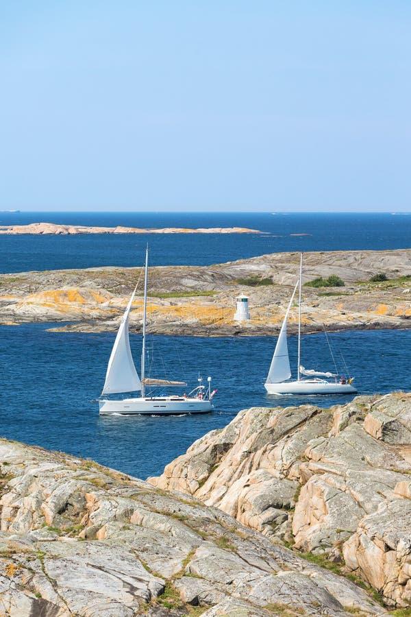 Sailboats sailing in rocky archipelago stock photography