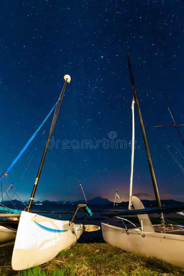 Sailboats on shore with a stars against the background stock photography