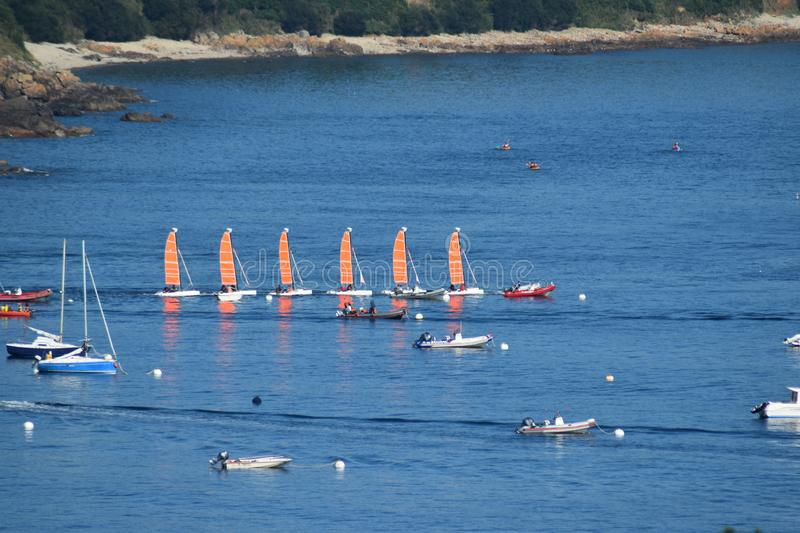 Sailboats in single file on the Breton sea in France stock photo