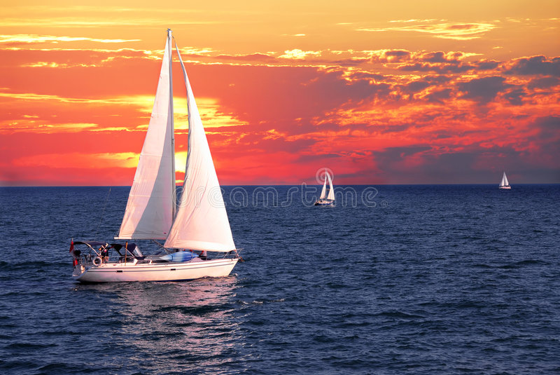 Sailboats at sunset royalty free stock photography