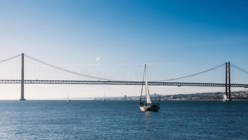 Sailboats with white sails on the Tagus River, 25 of April Bridge, Lisbon, Portugal stock photography
