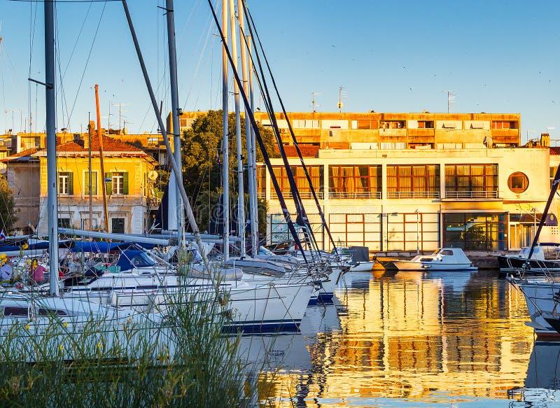 Sailboats in Zadar harbor at the sunset stock photo