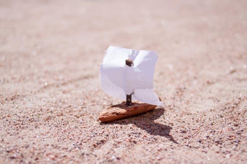 Sailer casalingo con la vela del Libro Bianco sul fondo della sabbia fotografia stock libera da diritti