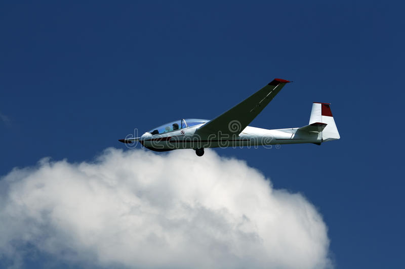 Sailflying. A glider shot against a dark blue sky and clouds stock image