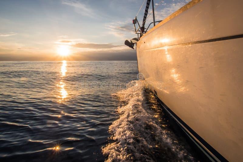 Sailin яхты к заходу солнца стоковое фото