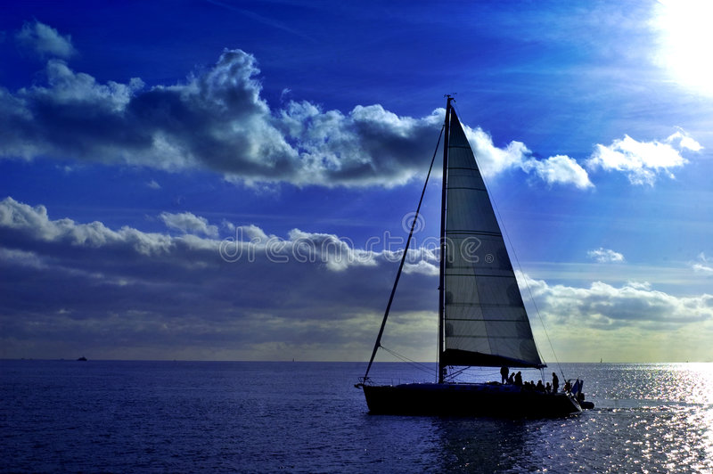 Sailing. A sailing boat is navigating with a blue sea and a blue sky