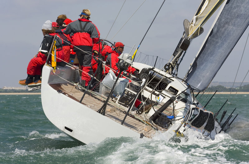 Sailing Away. A fully crewed racing yacht racing hard and leaving a big wake