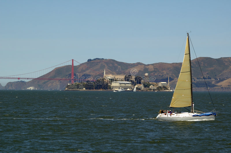 Sailing on the Bay. Yatch sailing on San Francisco bay with the Golden Gate bridge and Alcatraz in the distance with Marin Headlands behind royalty free stock photo
