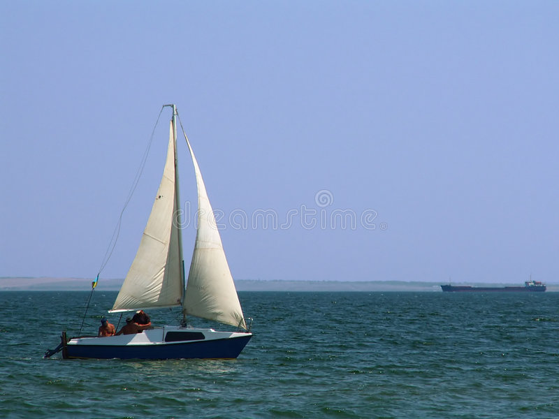 Sailing Boat. And container vessel on the background. There is 3 men aboard spending their vacations on the sea stock photos