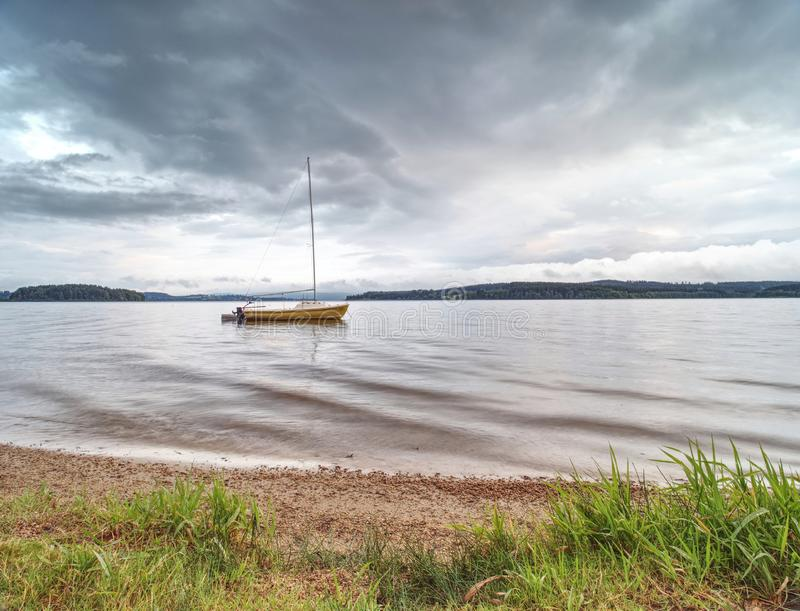 Sailing boat on calm waters. Empty yacht anchored at lake shore stock photos