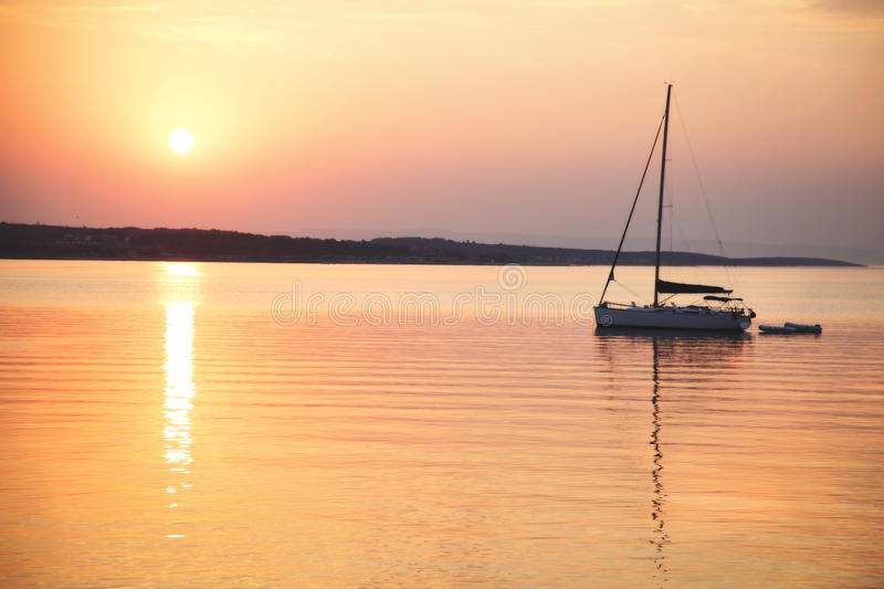 Sailing boat floats in the calm sea at sunrise stock image