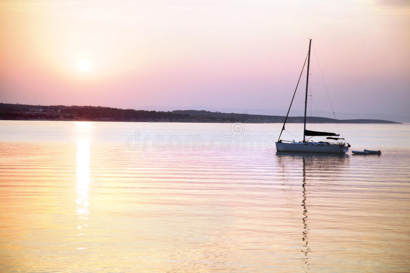 Sailing boat floats in the calm sea at sunrise royalty free stock images