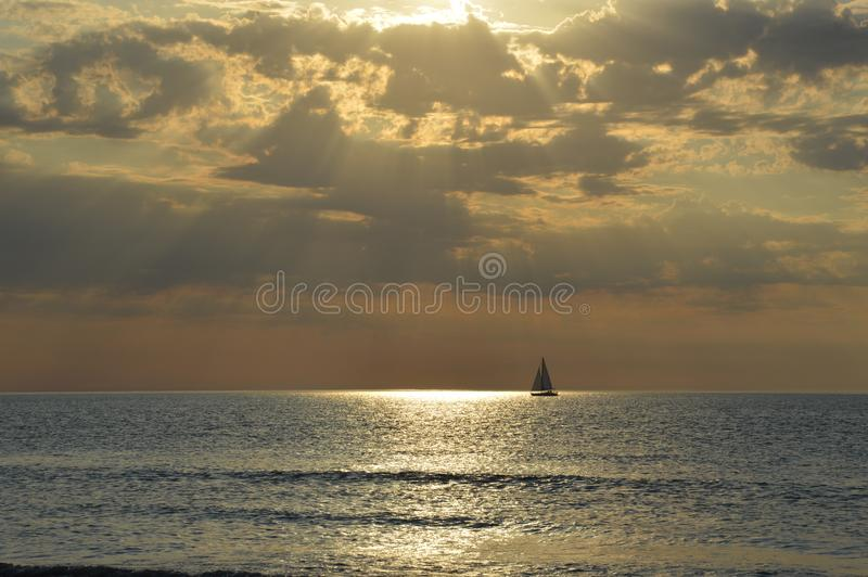 Sailing boat on the golden horizon line. Sailing boat on the horizon line of the Atlantic Ocean in Normandy, France. Enjoying beautiful nature, sea landscape stock photos