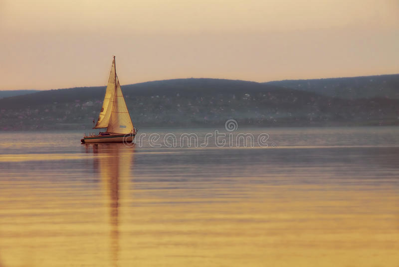 Sailing boat on the lake at sunset stock images