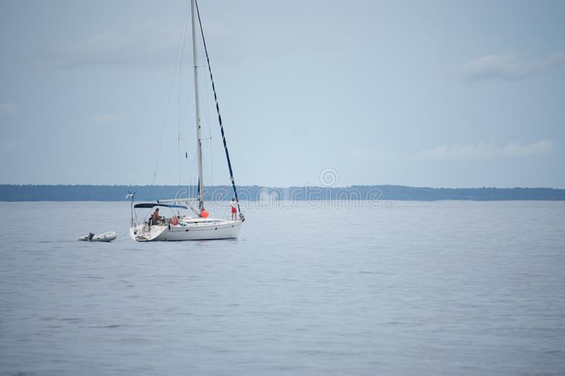 A sailing boat with people watching breaching whales in the distance in Eua in Tonga royalty free stock photos