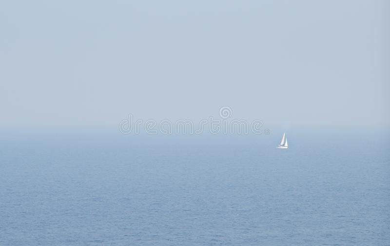 Sailing boat sailing on a calm sea with wind and fog.  stock photos