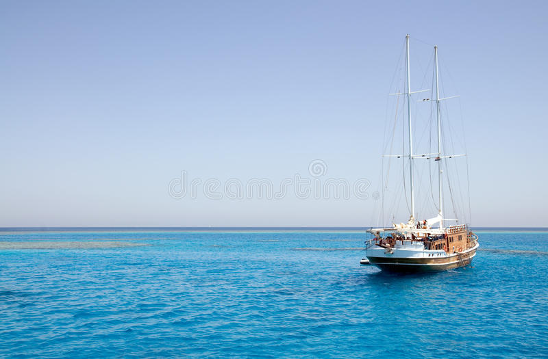 Sailing boat on sea. Isolated sailing ship on multicolored calm sea with coral reefs. Red Sea - Egypt, Africa stock image