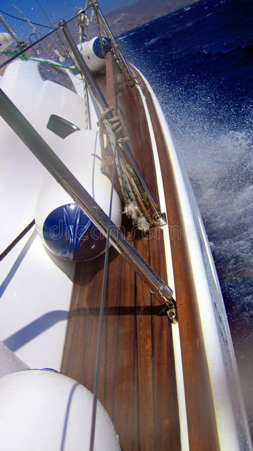 Sailing boat at sea. With spray from waves against the bow near the Cyclades islands in Greece royalty free stock image