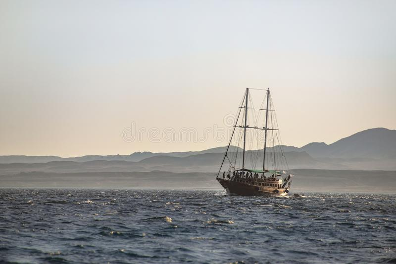 Sailing Boat at A Sea Journey with Mountains Beach in Background, Pirates Look, at Sunset stock photography