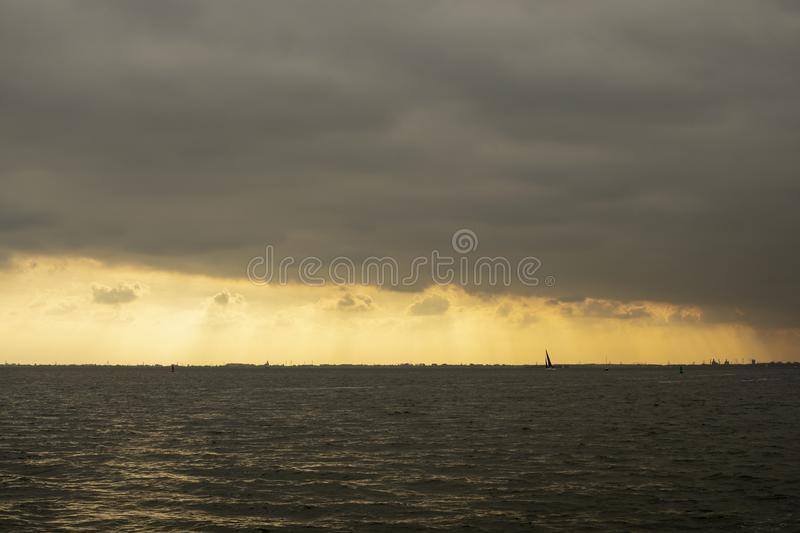 Sailing boat silhouette in front of the skyline of Amsterdam royalty free stock images