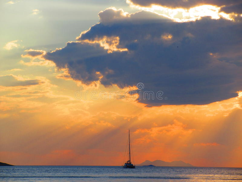 Sailing boat sunset. Warm orange rays of sunlight beam down on the ocean whilst a sailing boat provides the focal point royalty free stock image